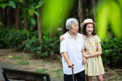 Den asiatiska lilla flickan som stöttar den höga kvinnan med den gå pinnen, den lyckliga le farmodern och sondottern i parkerar,  royaltyfria foton