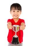 Den asiatiska lilla kinesiska flickan ler med en trofé i henne händer arkivbilder