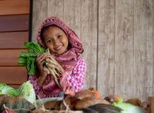 Den asiatiska lilla ung flickablicken fram?triktat och leendet bland olika typer av gr?nsaken rymmer ocks? r?disan bak h?nan p? t arkivbilder