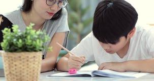Den asiatiska mamman hjälper hennes son att göra läxa