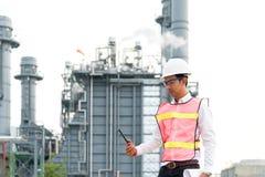 Den asiatiska manarbetaren och teknikerelektrikeren arbetar säkerhetskontroll på kraftverkenergibransch, folkarbete Thailand Royaltyfri Foto