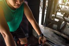 Den asiatiska mankroppsbyggaren med cykelmaskinvikter driver handsom royaltyfri foto