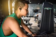 Den asiatiska mankroppsbyggaren med cykelmaskinvikter driver handsom arkivfoton