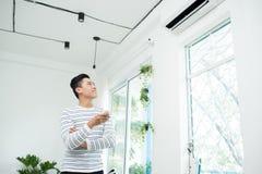 Den asiatiska mannen är det roterande luftvillkoret, genom fjärrkontroll och att le Royaltyfri Bild