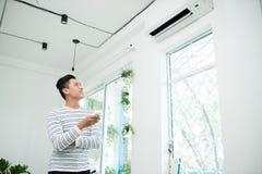 Den asiatiska mannen är det roterande luftvillkoret, genom fjärrkontroll och att le arkivbilder
