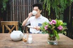 Den asiatiska mannen dricker te Arkivfoto
