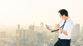 Den asiatiska mannen firar med smartphonen, framgång, eller bifallet poserar på plats för taksolnedgångstad royaltyfria foton