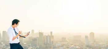 Den asiatiska mannen firar med smartphonen, framgång, eller bifallet poserar på taket, solnedgångstadsplats royaltyfri foto