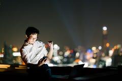 Den asiatiska mannen firar med smartphonen, och bärbar datordatoren, framgång poserar Affär, jobb eller begrepp för kommunikation arkivbilder