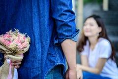 Den asiatiska mannen har att förbereda sig och att vänta med blomman för att säga ledsen Royaltyfri Fotografi