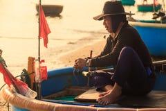 Den asiatiska mannen i hatt sitter i runt fartyg och reder ut fisknät Royaltyfri Bild