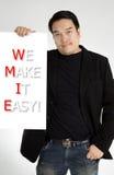 Den asiatiska mannen i svart dräkt med GÖR VI IT LÄTT! meddelande på vit b royaltyfria bilder