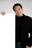 Den asiatiska mannen i svart dräkt rymmer en tom platta arkivfoton
