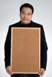 Den asiatiska mannen i svart dräkt rymmer en tom woodboard royaltyfri bild