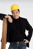Den asiatiska mannen i svart dräkt rymmer en tom woodboard royaltyfria bilder
