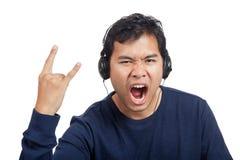Den asiatiska mannen lyssnar till vaggar musik med headphonen Arkivbild