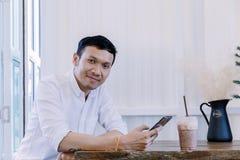 Den asiatiska mannen som använder ett mobiltelefon- och drinkkaffe i bageri, shoppar Arkivbild