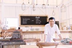 Den asiatiska mannen som bär ett vitt skjortaanseende i bageri, shoppar fotografering för bildbyråer
