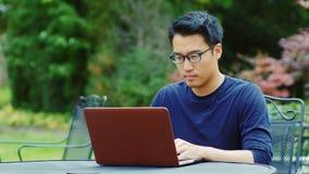 Den asiatiska mannen som bär exponeringsglas, arbetar med en bärbar dator lager videofilmer