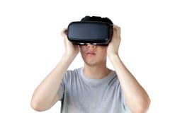 Den asiatiska mannen som bär VR, rullar med ögonen och fördjupar sig i VR-multimedia Arkivbild
