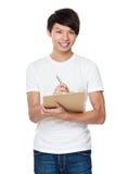 Den asiatiska mannen tar anmärkningen på skrivplattan Arkivfoto