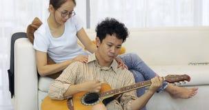 Den asiatiska manserenadälsklingen med gitarrkvinnan ser pojkvännen lager videofilmer
