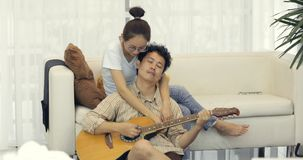 Den asiatiska manserenadälsklingen med gitarrkvinnan ser pojkvännen arkivfilmer