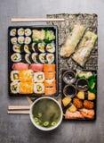 Den asiatiska matmenyuppsättningen med sushi, ny sommar rullar och misosoppa på Nori och grå färgstenbakgrund royaltyfri bild