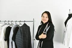 Den asiatiska modeformgivaren som arbetar i hennes visningslokalstudio, kvinnlig i märkes- kläder, shoppar Royaltyfri Fotografi