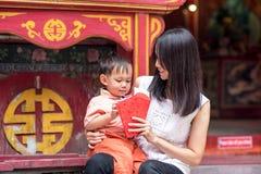 Den asiatiska modern ger det röda kuvertet eller Ang-powen till sonen Arkivfoton