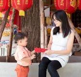 Den asiatiska modern ger ett röd kuvert eller Ang-pow till sonen arkivfoto