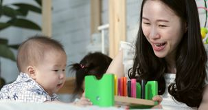 Den asiatiska modern kan barnet som spelar på sängen med leendeframsidan stock video