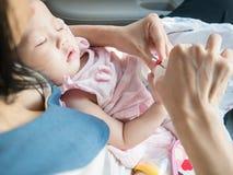 Den asiatiska modern klippte hennes babys spikar, medan behandla som ett barn sömn Arkivfoto