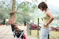 Den asiatiska modern med henne 7 gammala månad behandla som ett barn flickan Arkivfoton