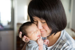 Den asiatiska modern med nyfött behandla som ett barn i sjukhuset Fotografering för Bildbyråer