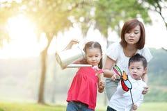 Den asiatiska modern och barn som spelar på utomhus-, parkerar royaltyfri foto