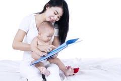 Den asiatiska modern och behandla som ett barn läsa en isolerad bok - Royaltyfria Bilder