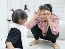 Den asiatiska modern som gör rolig gest för att hålla hennes för att behandla som ett barn flickan, underhöll, medan vänta för at arkivbilder