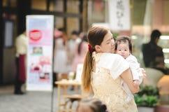 Den asiatiska modern som kramar henne, behandla som ett barn utomhus Royaltyfria Bilder