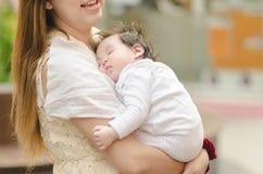 Den asiatiska modern som kramar henne, behandla som ett barn utomhus Fotografering för Bildbyråer