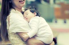 Den asiatiska modern som kramar henne, behandla som ett barn utomhus Royaltyfria Foton