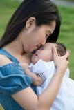 Den asiatiska modern som kysser det gulligt, behandla som ett barn Arkivbild