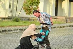 Den asiatiska muslim den hijabimodern och fadern går till och med parkerar med sonen i sittvagn medan hans mamma som tar omsorg a arkivfoton