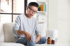Den asiatiska pensionären med knäet smärtar Royaltyfri Bild