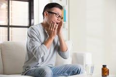 Den asiatiska pensionären med munnen smärtar Arkivfoto