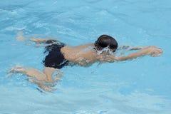 Den asiatiska pojkebröstslaglängden simmar i simbassäng Royaltyfria Bilder