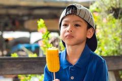 Den asiatiska pojken äter grillad havre arkivfoto