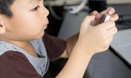 Den asiatiska pojken använder smartphonen för att spela lekar Arkivbild