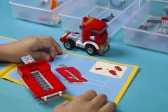 Den asiatiska pojken bygger lego med anvisningshandboken Arkivfoton