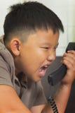 Den asiatiska pojken grälar på på telefonen Arkivbild